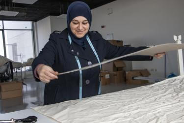 Jordanian woman measures textiles in workspace.