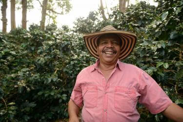 A person wearing a large brim hat smiles for the camera in a lush environment.