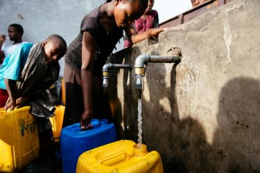 Young people fill water vessels.