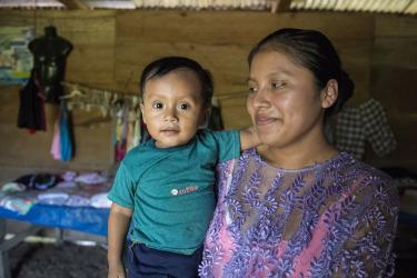 A mother holds their baby inside their home in guatemala.