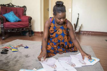 A fashion designer looks through some of her sketches on the floor of her apartment in the pangani area of nairobi.