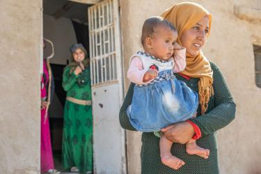 A person holds a child in front of their mother's home.
