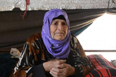 An elderly adult sits with their hands clasped.