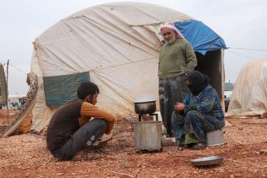 Two individuals sit in front of their tent in al-rayyan camp while speaking with an adult.