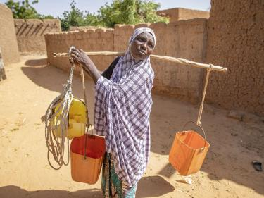 Halma, pictured in a purple and white shawl carrying three buckets balanced across her shoulders on a large stick