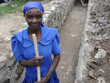 Haitian woman pictured cleaning and renovating a drainage ditch.
