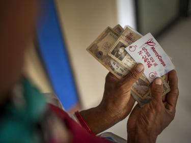 Image: hands holding cash and a mercy corps id card during a distribution of emergency cash