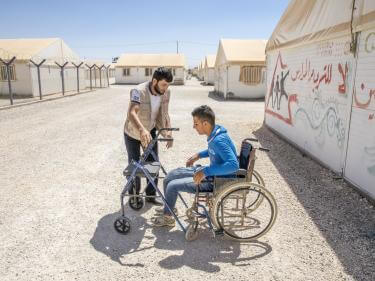 A mercy corps team member works with a young man who uses mobility equipment at a refugee camp in jordan