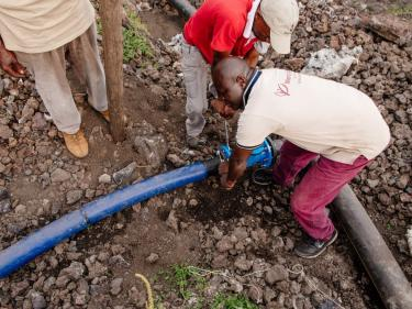 Men work to connect water pipes in dr congo