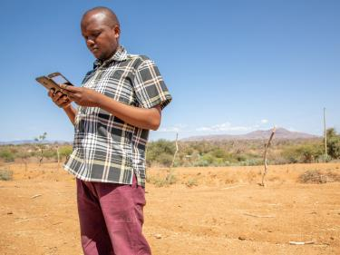 Kenyan man looking at his mobile phone