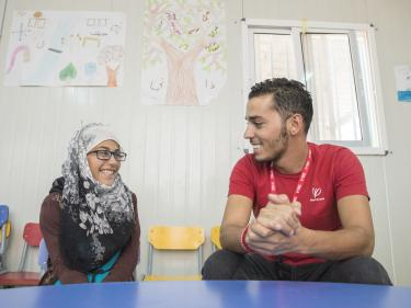 A mercy corps staff member sits at a table smiling with a young participant in azraq, jordan.