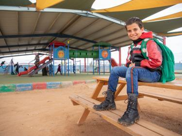 A young boy sitting at a playground in jordan