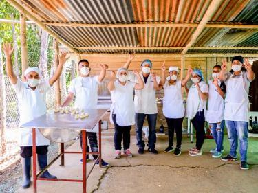 A group of bakers wave at the camera from an outdoor kitchen.