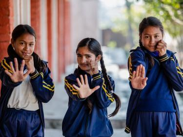 Three nepalese girls pose with hands out in front of them.