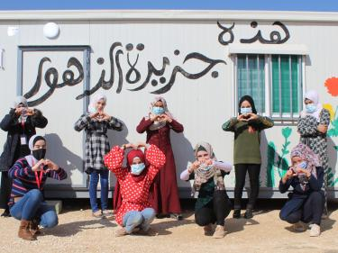 A group of young people pose together outside a temporary structure they designed and decorated themselves.