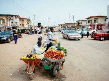 People selling fruits and vegetables on a busy street.